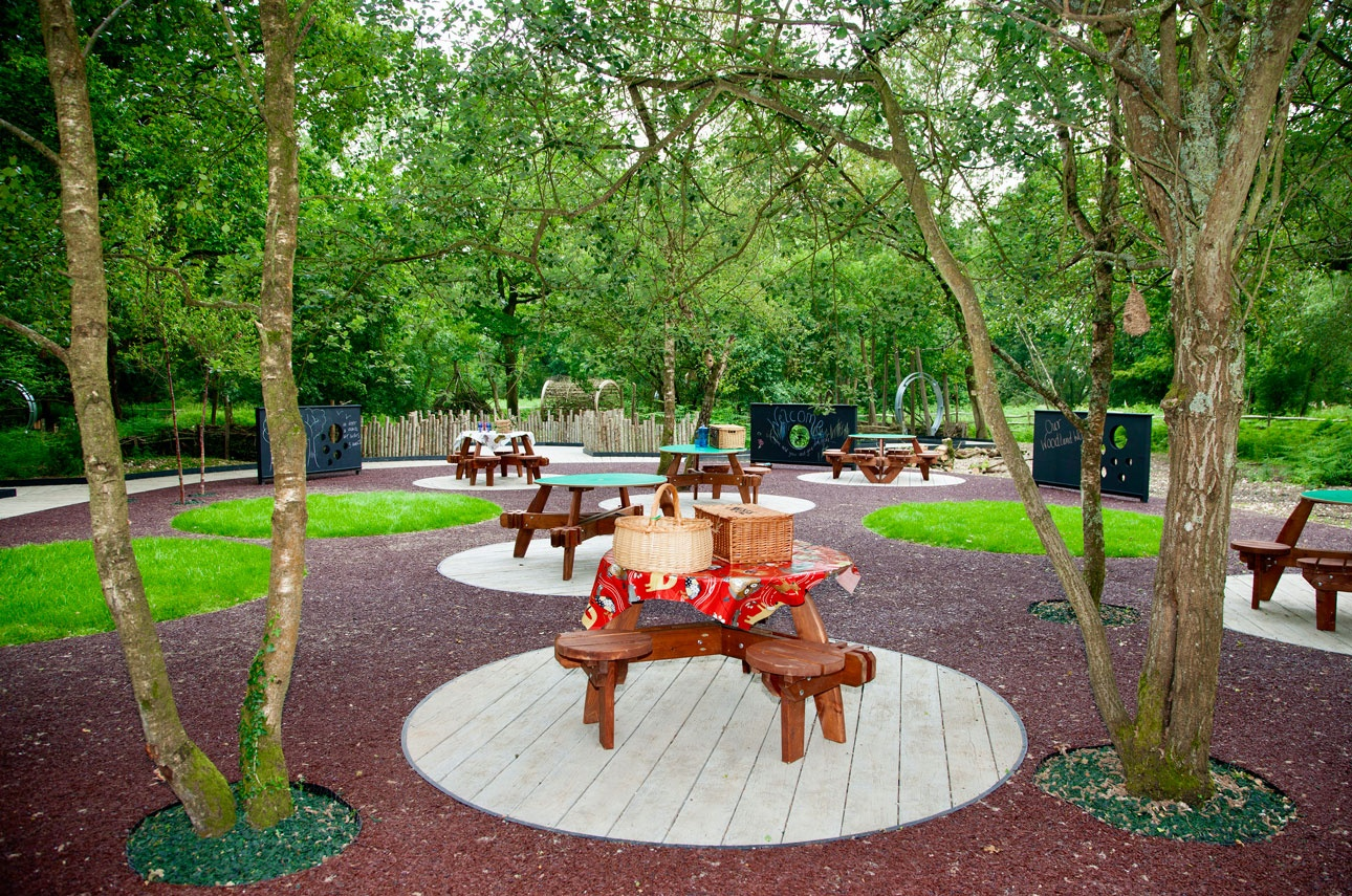 Fun family picnic area with timber tables and bench seating on circular decks under a canopy of multistem trees