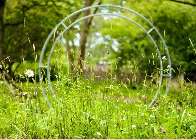 Steel moongate arch in wildflower meadow in hospice garden designed by Ann-Marie Powell Gardens