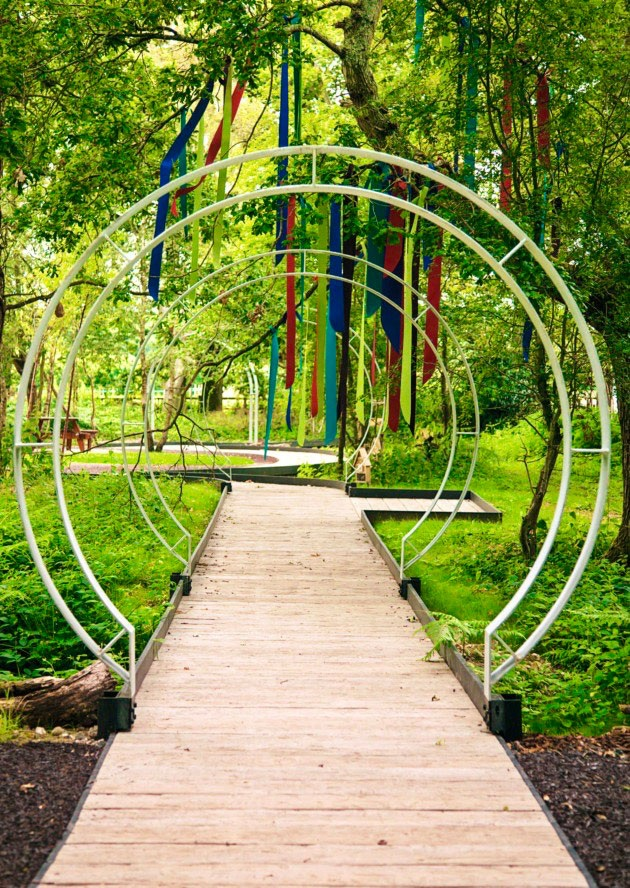Steel moongate arches under tree festooned with colourful ribbons along timber boardwalk