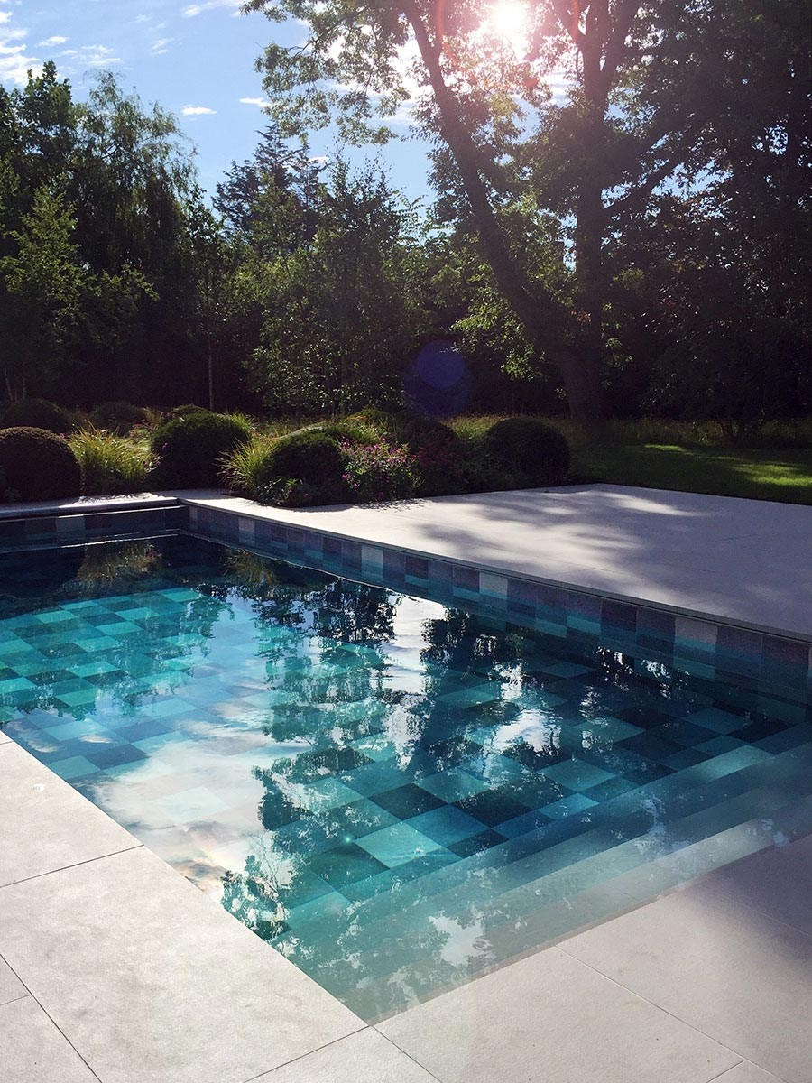 Tiled swimming pool in large private garden, Hampshire with porcelain paving; terrace, pool, planting plans designed by AMPG.