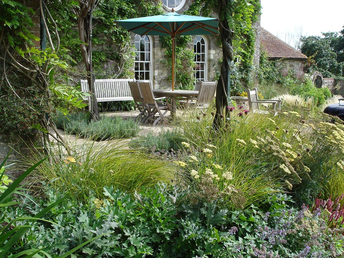 Grasses, achillea, acanthus, monarda around York stone terrace, with wisteria pergola from garden designers Ann-Marie Powell.