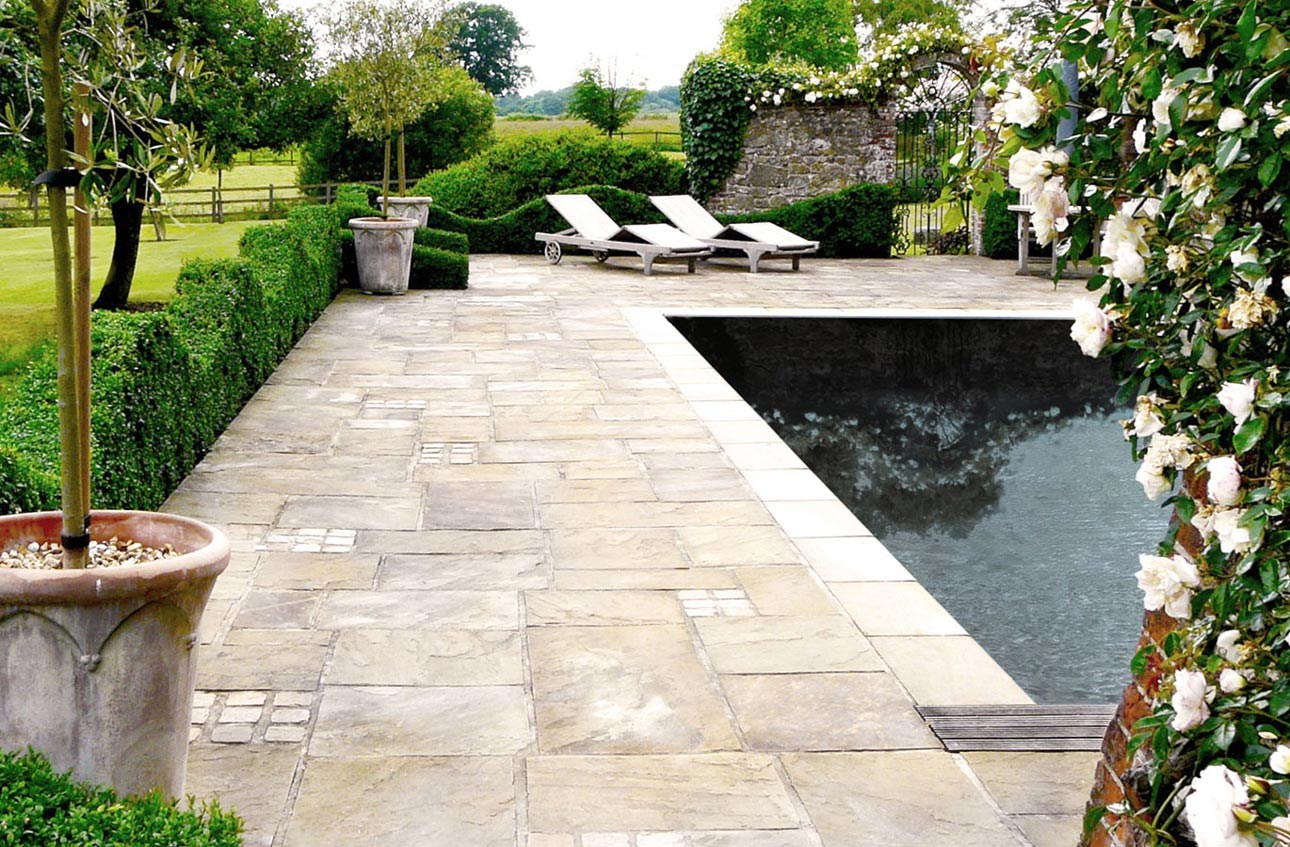 York stone paving in swimming pool garden with terracotta pots, topiary box hedging plants and climbing roses, West Sussex.
