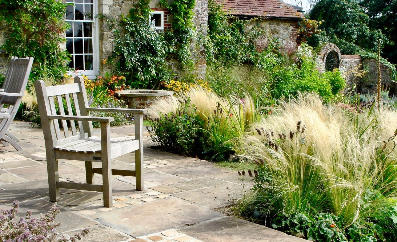 Timber garden chair on york stone paving and sett terrace, patio with stipa tenuissima by garden well, by Ann-Marie Powell.