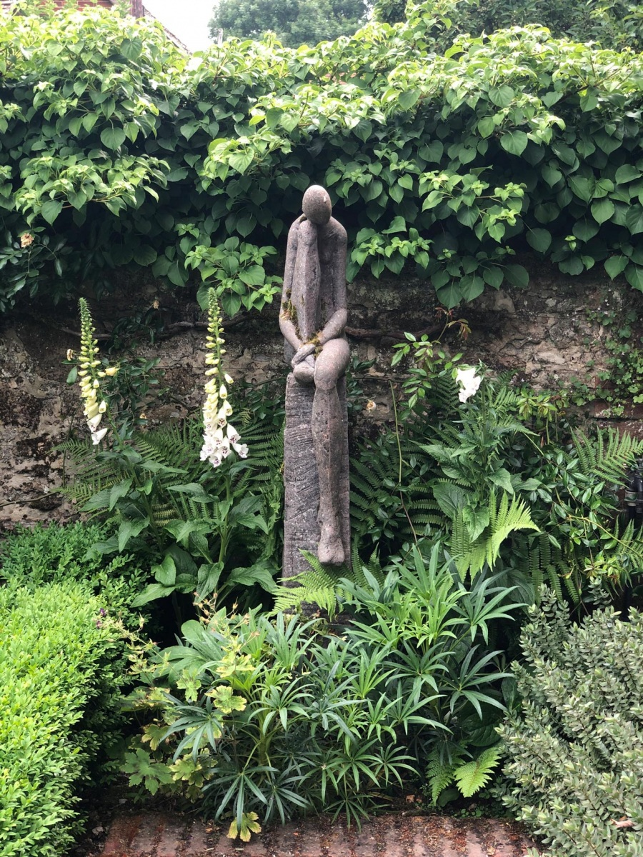 Helen Sinclair Sculpture with hellebores, ferns and foxgloves against garden wall with climbing hydrangea. Design by AMPG.