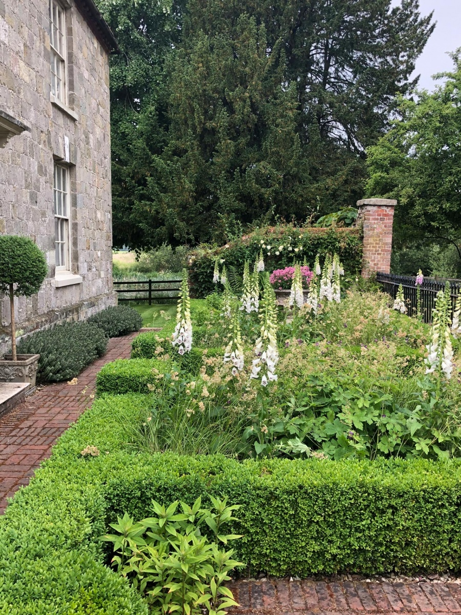 Brick piers and path pavers with clipped box, hebe hedging, iron railings in small front garden by Ann-Marie Powell Gardens.