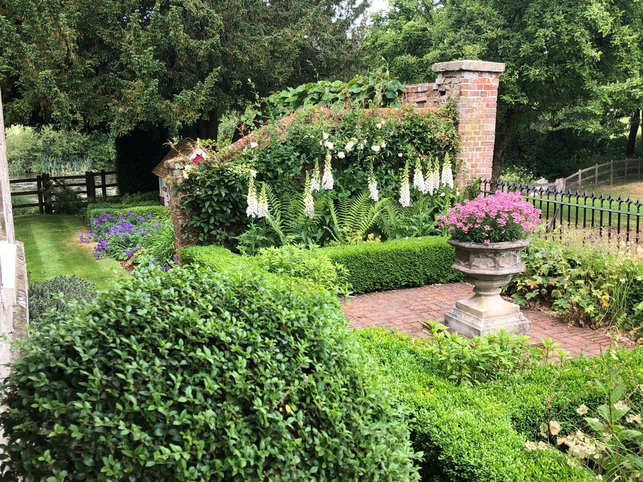 Sheltered front garden courtyard with brick walls, paths, box hedging, foxgloves and ferns planting design by Ann-Marie Powell