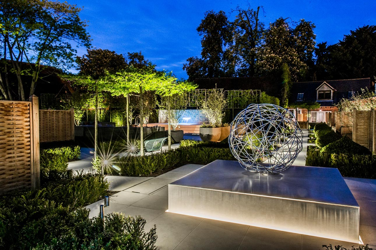 Contemporary hotel garden design at night with garden lighting design by Petersfield garden designer Ann-Marie Powell.