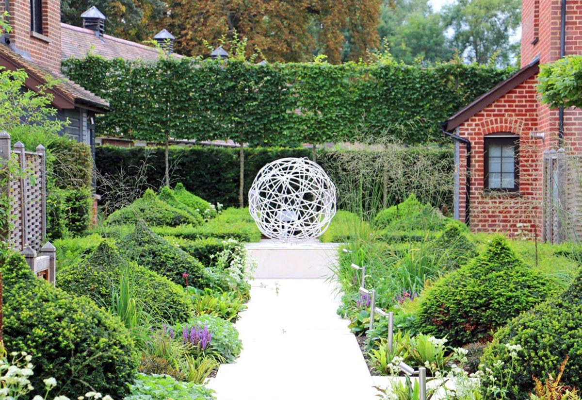 Topiary garden with yew, Taxus baccata, clipped domes in double herbaceous borders at The Mews, Sopwell House, Hertfordshire.