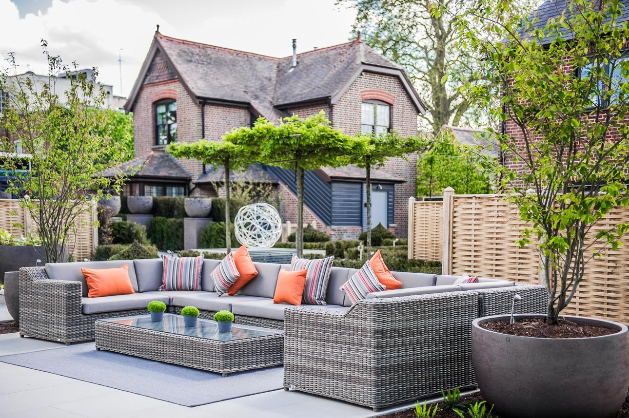 Garden sofas in outdoor relaxation garden with large pots of Amelanchier lamarckii by Ann-Marie Powell Gardens, Hampshire.