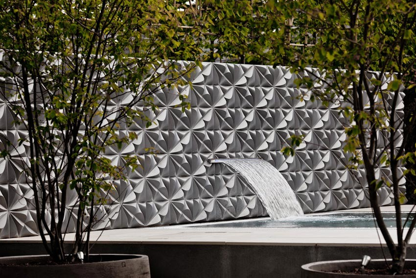 Feature garden wall with water blade above hot tub at hotel garden by Ann-Marie Powell Gardens, Petersfield, Hampshire.