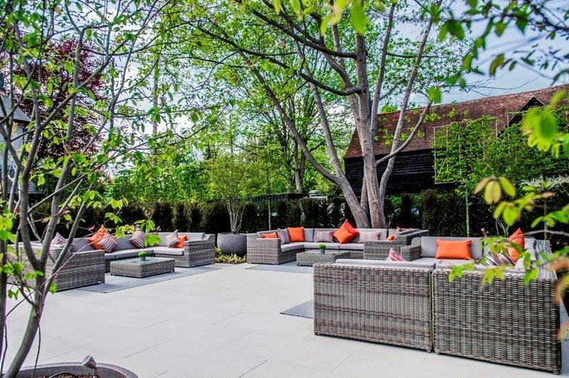 Outdoor relaxation area with Manutti garden sofas and rugs at hotel garden, St. Albans, Hertfordshire by Ann-Marie Powell.