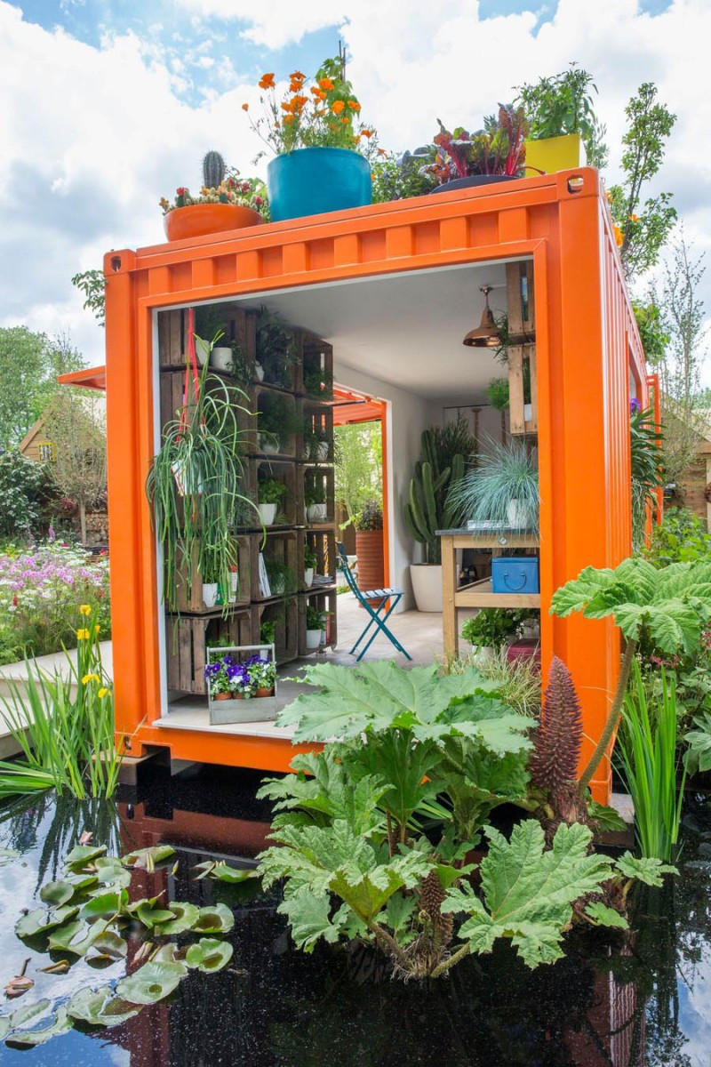 Orange shipping container topped with colourful edible planters next to pond planted with water lilies, iris and Gunnera