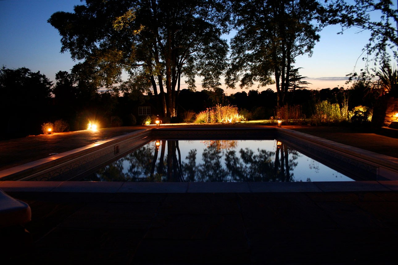 Dramatic lighting highlighting the planting around a contemporary black lined pool, by Ann-Marie Powell Gardens