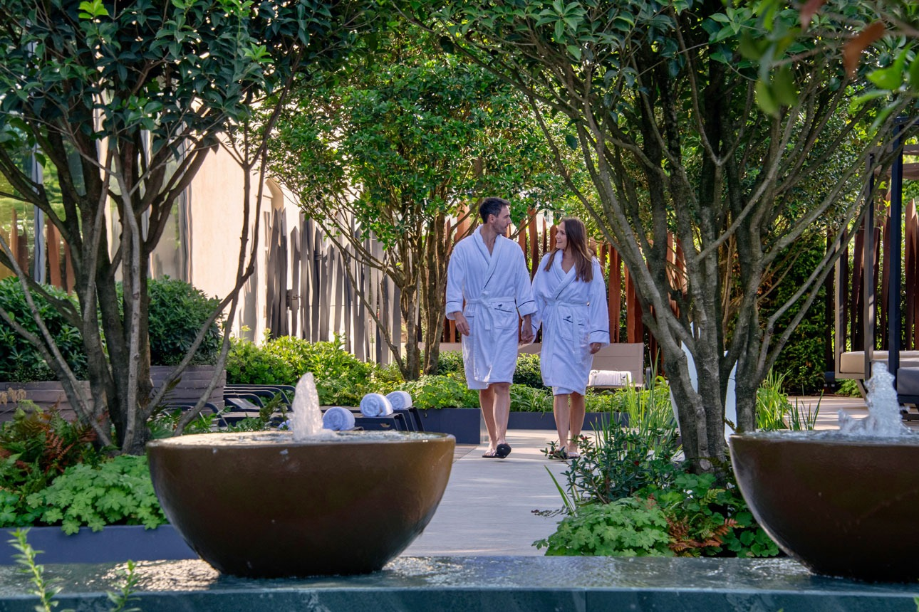 Multistem feature rhododendron shrubs in private spa garden with luxuriant loungers, leading to bespoke water feature