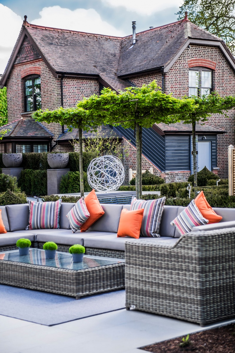 Rattan effect modular sofa accessorised with colourful garden cushions, parasol pleached trees and commisisoned sculpture