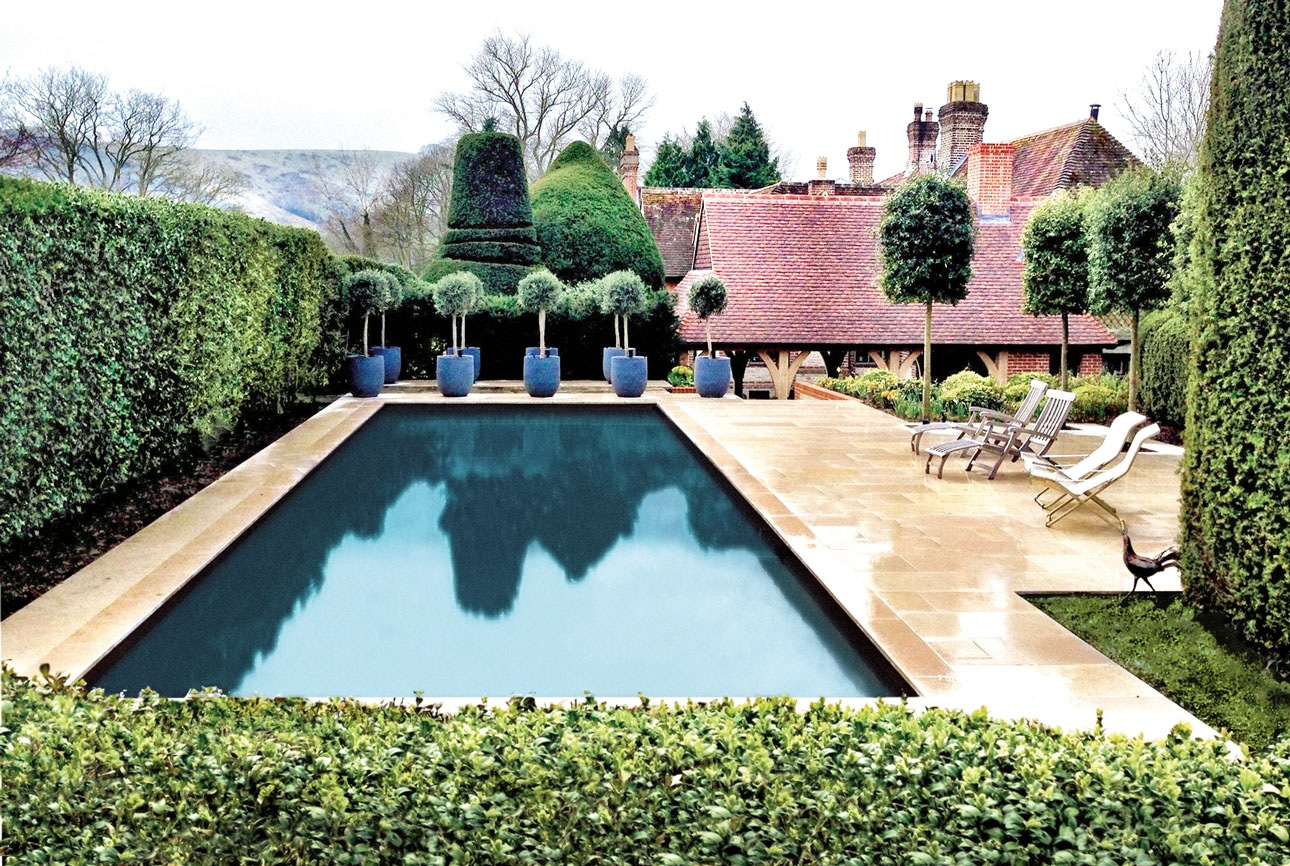 Swimming pool in large country garden in warm sandstone paving, surrounded by soaring topiary domes on clear stems