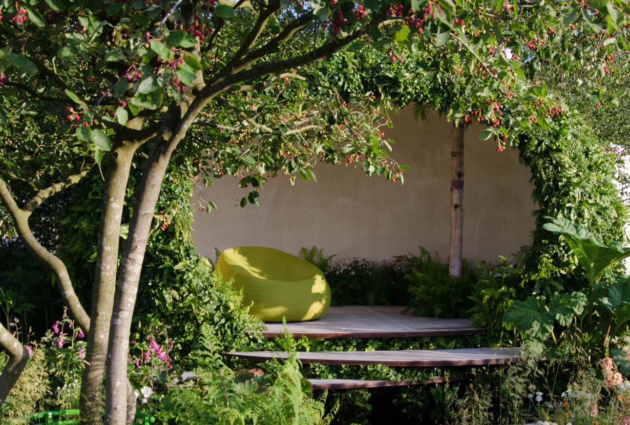 Red berries on multistem tree in front of restful seating structure in gold medal winning garden designed by Ann-Marie Powell