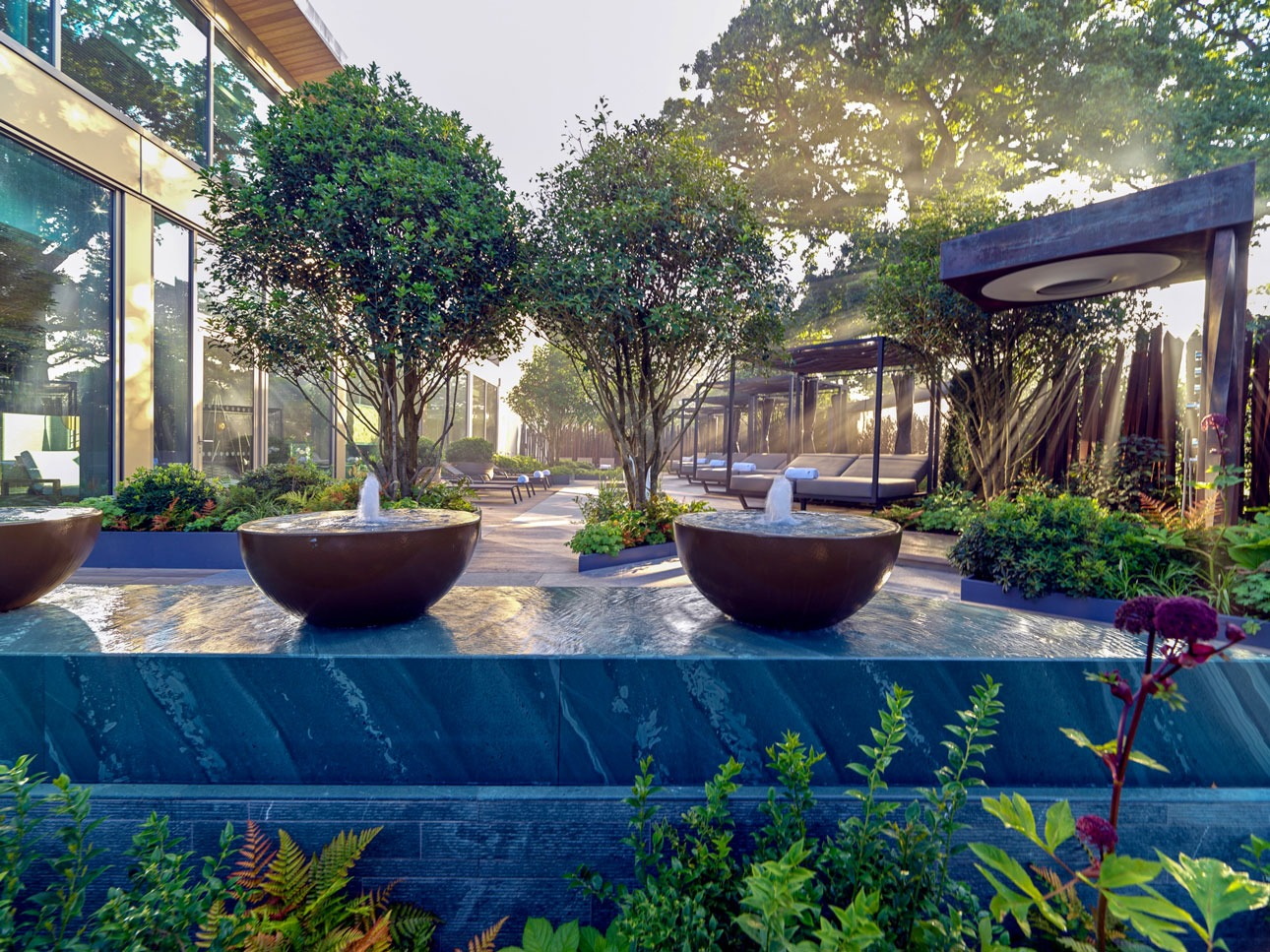 Contemporary water feature bowls with bubble fountain over green slate water table in luxury spa garden designed by AMPG