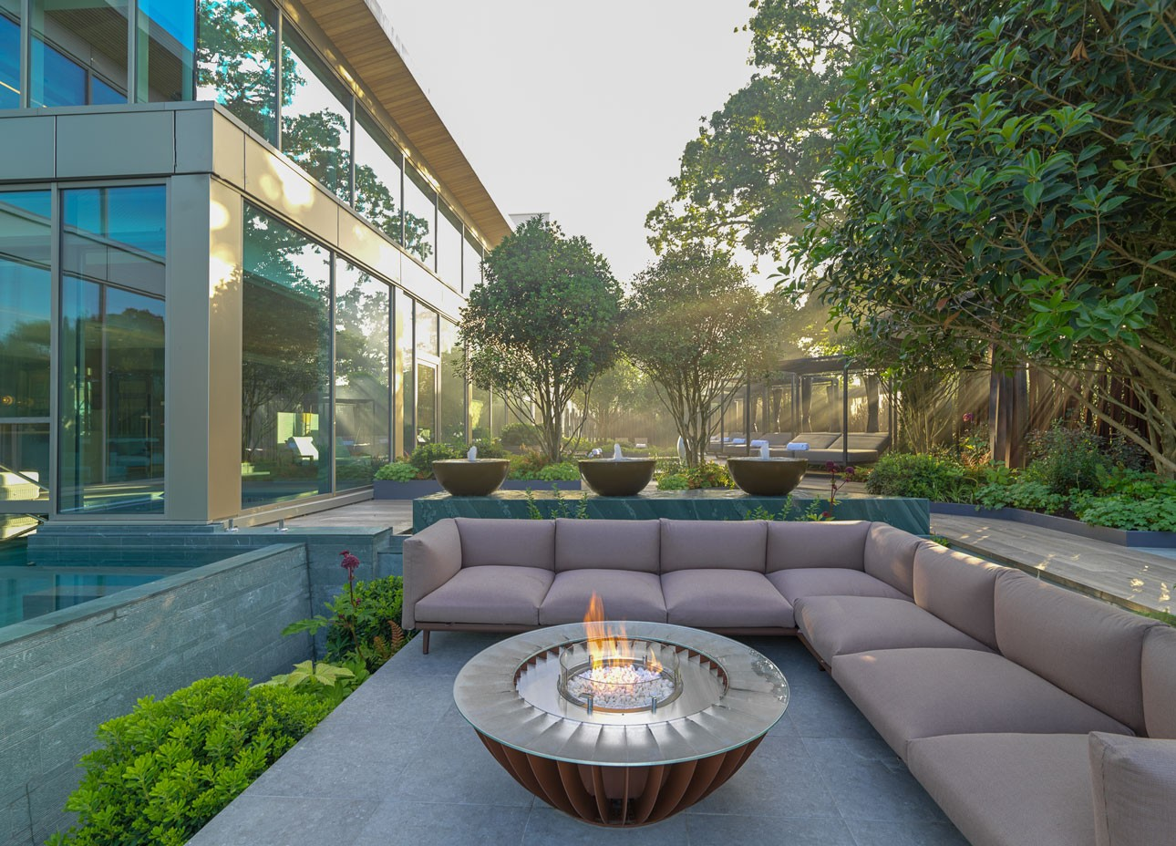 Bespoke firebowl and corner sofa beside luxury spa slate lined swimming pool in front of custom designed water feature