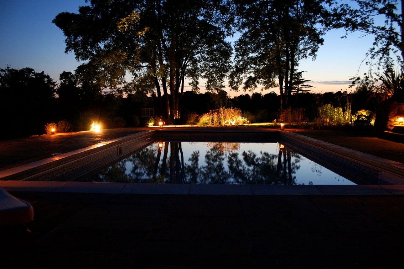Swimming pool at night reflecting mature trees and existing landscape. Lighting design highlighting feature plants