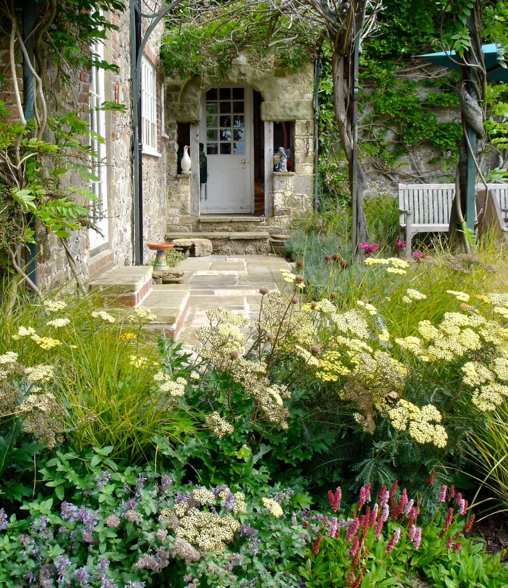 Contemporary planting design with pink persicaria, yellow achillea flowers, seedheads and grasses by Ann-Marie Powell Gardens