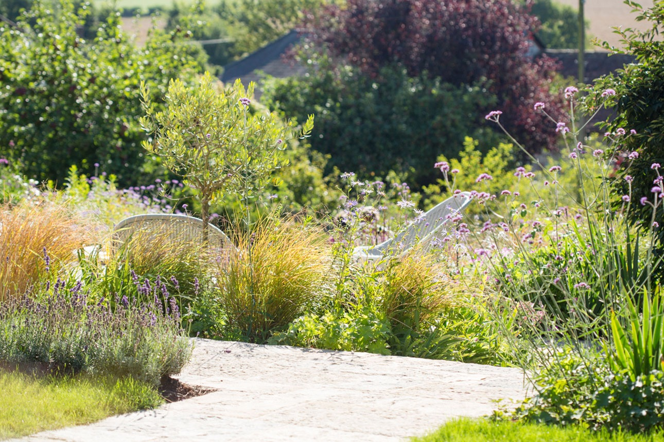 Riven limestone paving leading to seating area surrounded by mixed perennial planting designed by Ann-Marie Powell