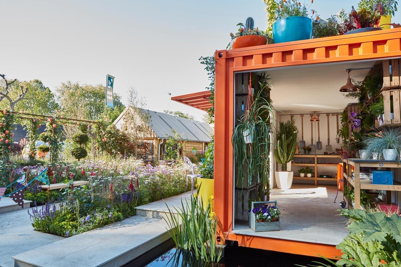 Urban garden with orange shipping container studio, naturalistic planting by Ann-Marie Powell Garden design studio, Hampshire.