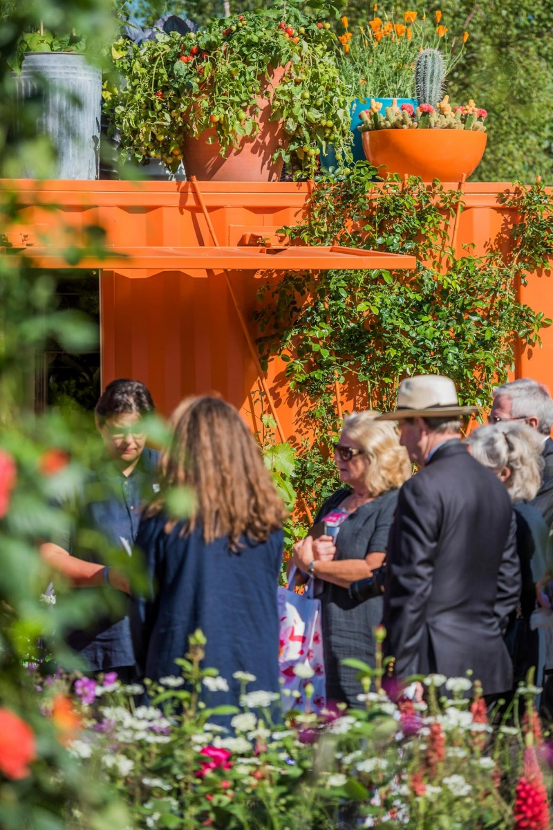 Orange shipping container potting shed or studio at RHS Chelsea with container vegetable garden on roof, designer AMPG.