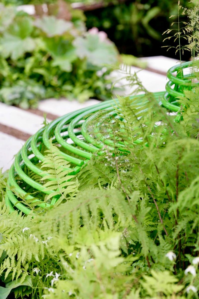 Contemporary powder coated steel benches with ferns on Macmillan Garden at RHS Hampton Court; designed by Ann-Marie Powell.