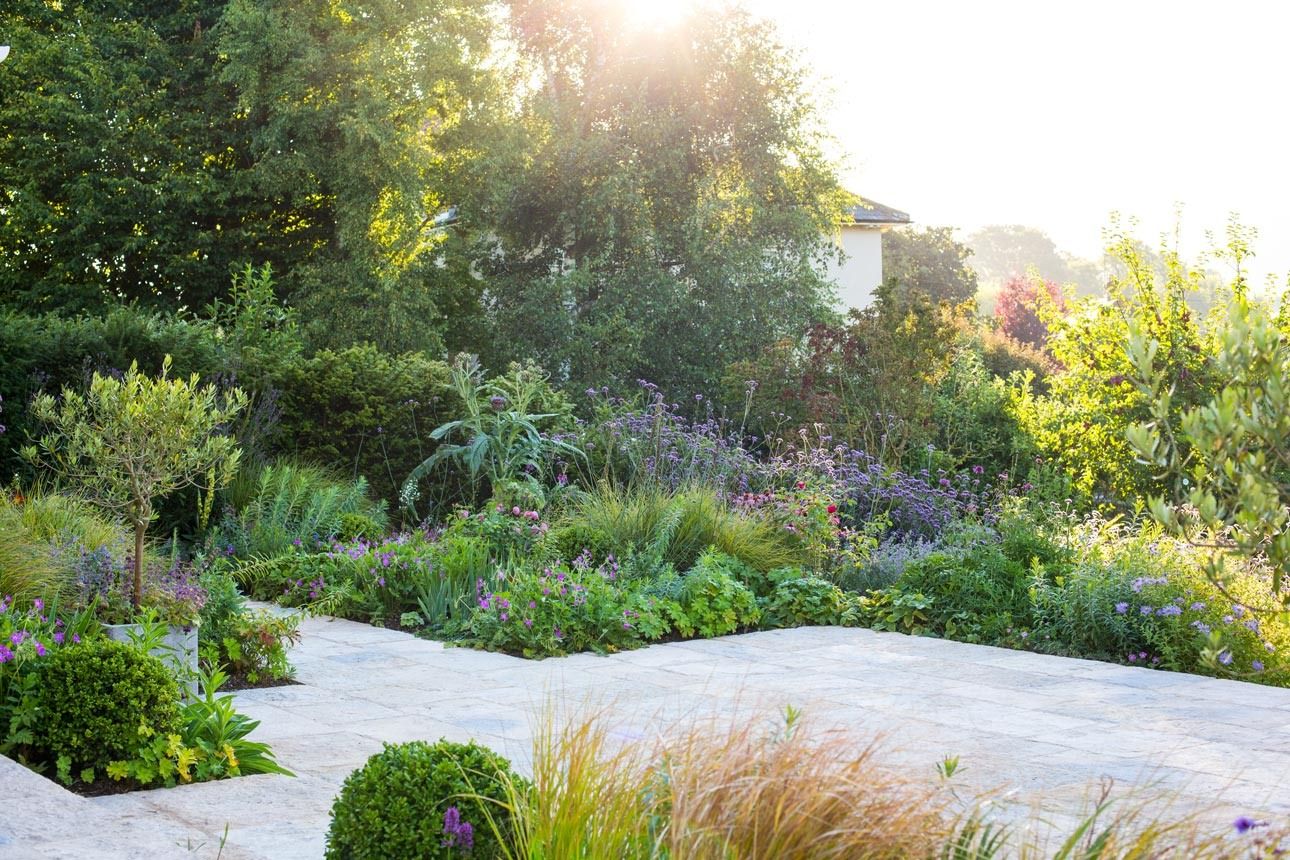 Late summer flower border in purples, pinks with Purbeck stone terrace, informal planting designs by Ann-Marie Powell Gardens.