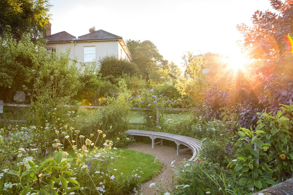 Circular timber bench with lawn and meadow for biodiversity and wildlife designed by Ann-Marie Powell Gardens, Hampshire.