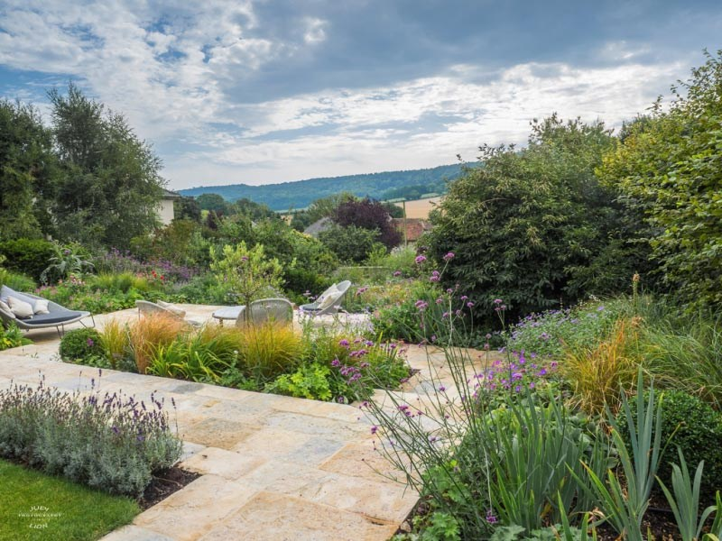 Garden paving in Purbeck stone on patio overlooking West Sussex hills; planting designers Ann-Marie Powell Gardens.