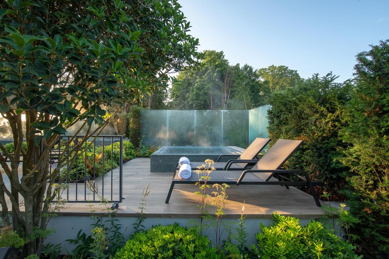 Glass walls around bespoke hot tubs with garden loungers, commercial spa garden design from Ann-Marie Powell Gardens