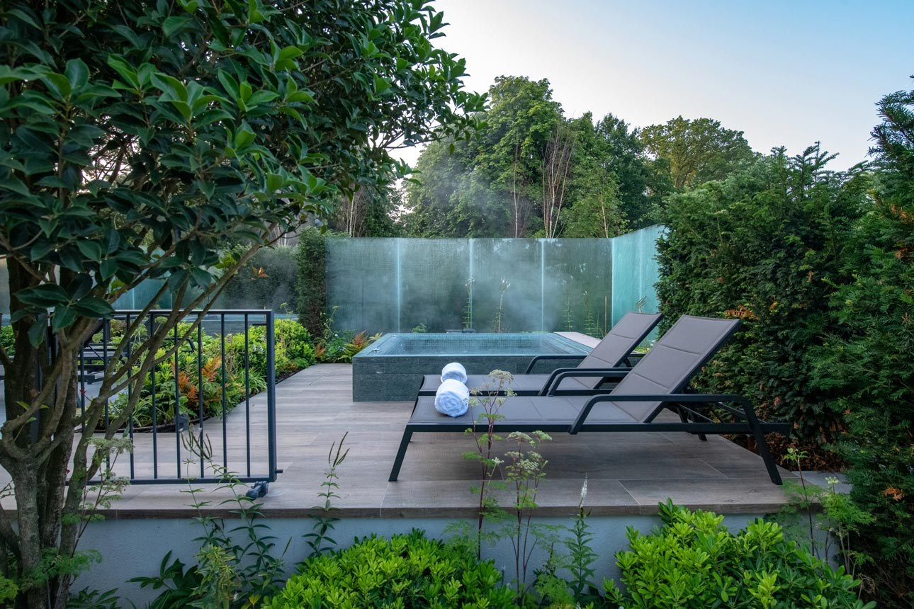 Mature hedging plants and bespoke glass walls around hot tubs in relaxing gardens in Hertfordshire at Cottonmill spa.