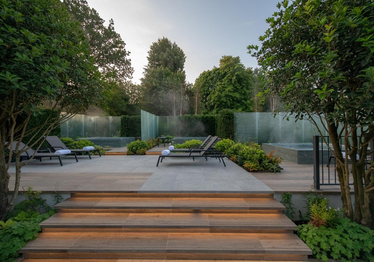 New gardens at Cottonmill spa with glass walls, hot tubs, and infinity LED lighting designed on the porcelain step detail.