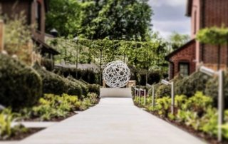 Garden sculpture with yew topiary in luxury hotel garden designed by Ann-Marie Powell