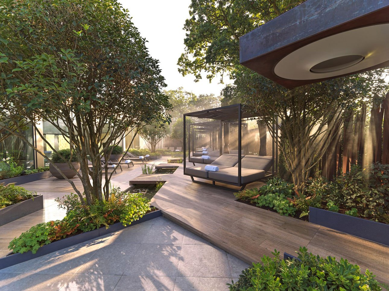 Bespoke day beds beside water rill with porcelain paving and mature Osmanthus aquifolium, pittosporum in shade planting
