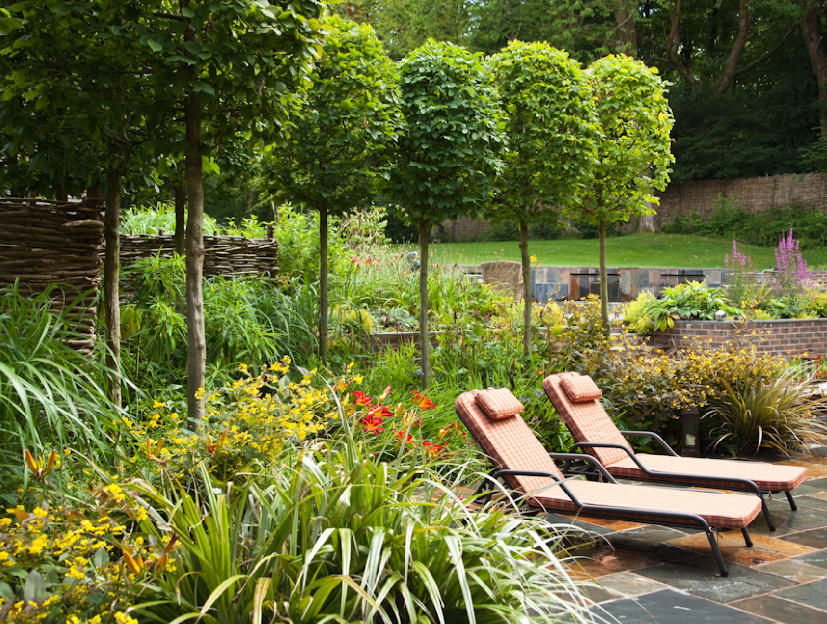 Lollipop trees with bold contemporary planting and sun loungers on a rustic slate terrace