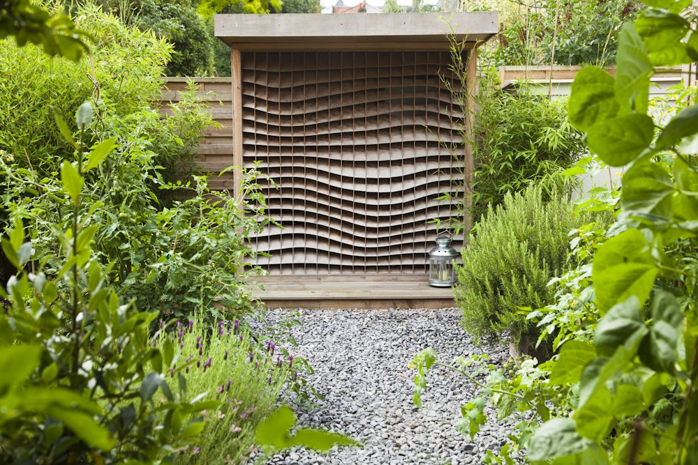 Bespoke contemporary potting shed in front of raised beds planted as edible potager vegetables, herbs and flowers