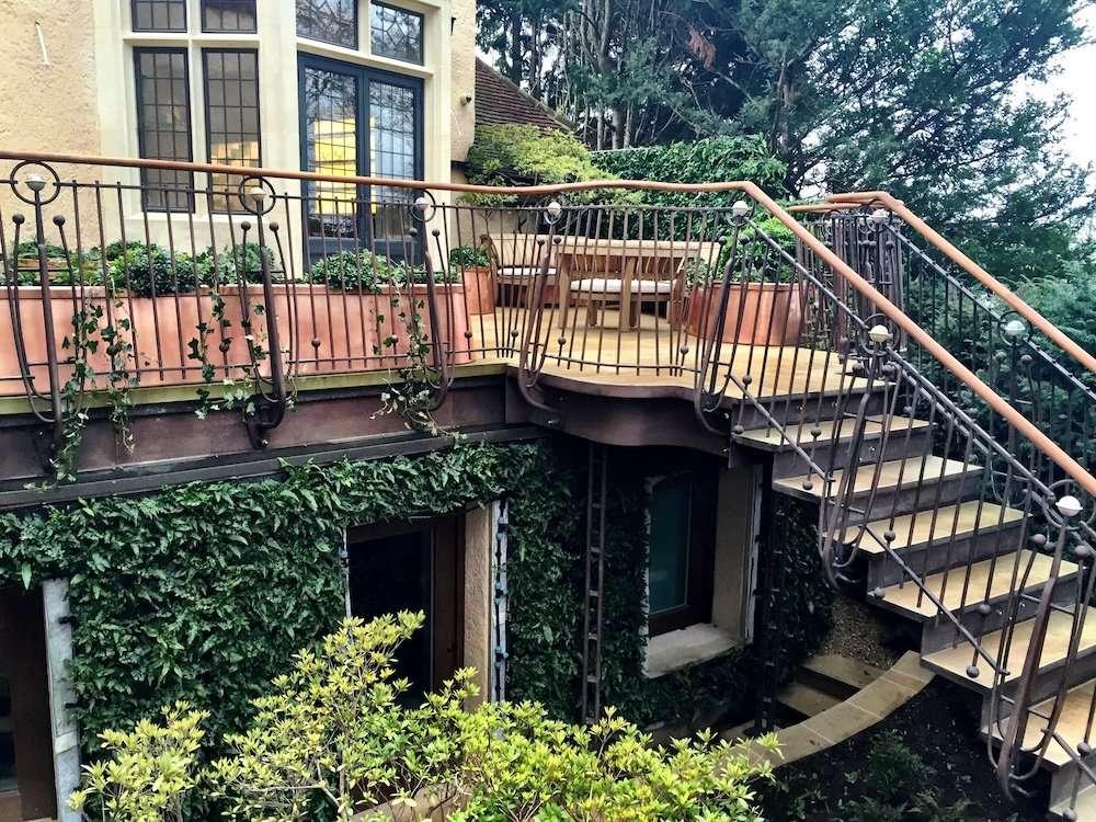 Balcony roof terrace enclosed by bespoke wrought iron railings, custom copper planters with multistemmed azalea framing door