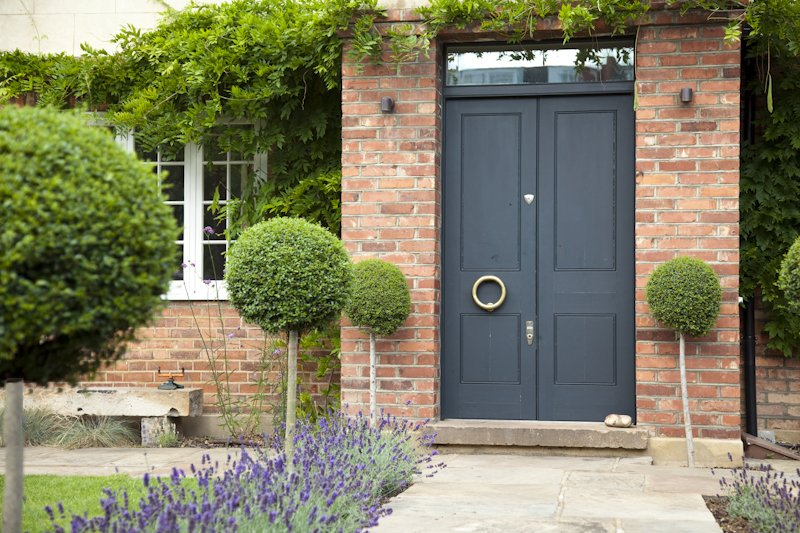 Front garden design with Ligustrum topiary lollipops lining reclaimed york flag stone path to front door edged with lavender