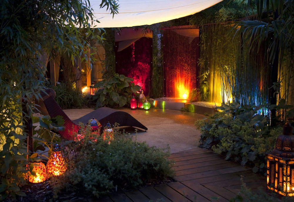 Coloured acrylic water sheets creating dramatic water wall feature in a courtyard garden designed by Ann-Marie Powell Gardens
